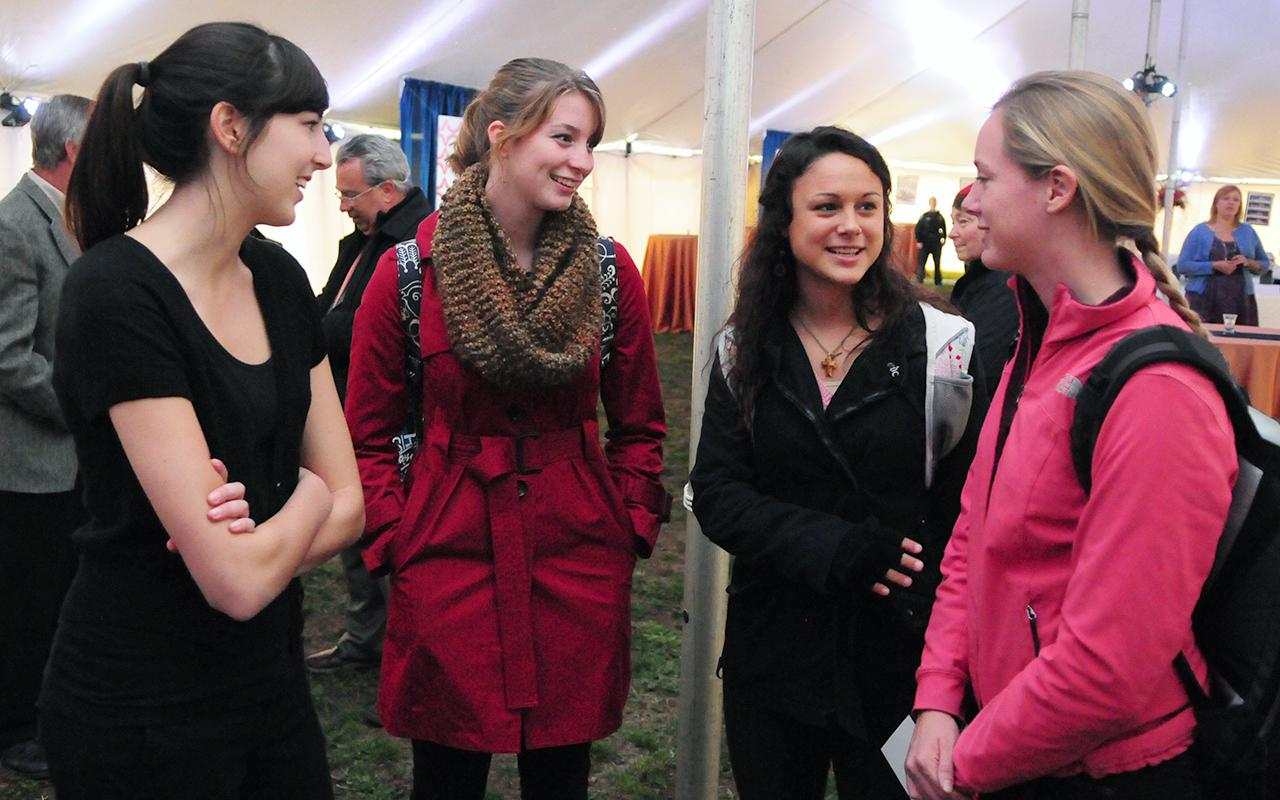 Four students conversing with each other inside the tent.