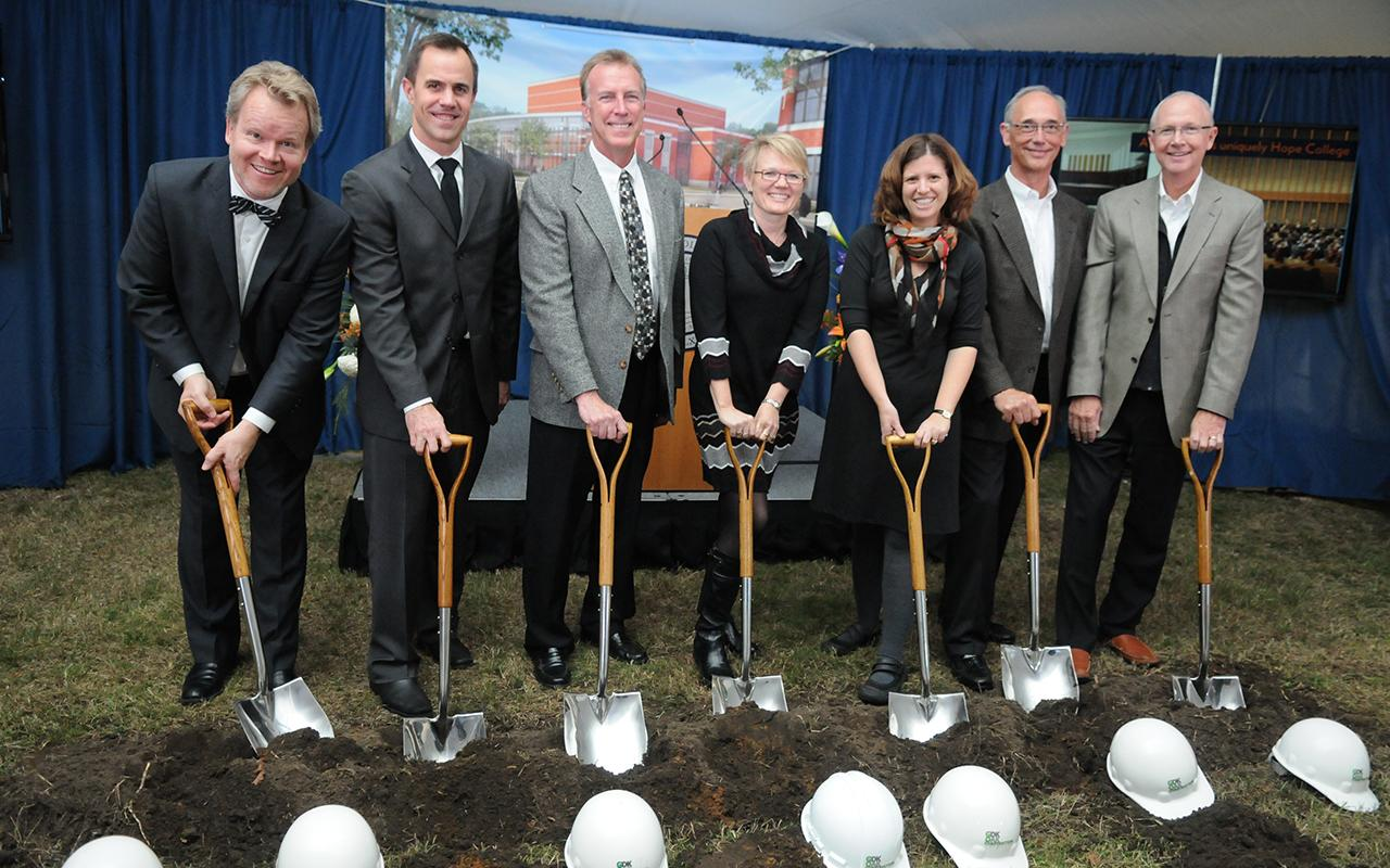 Seven people pose with shovels.