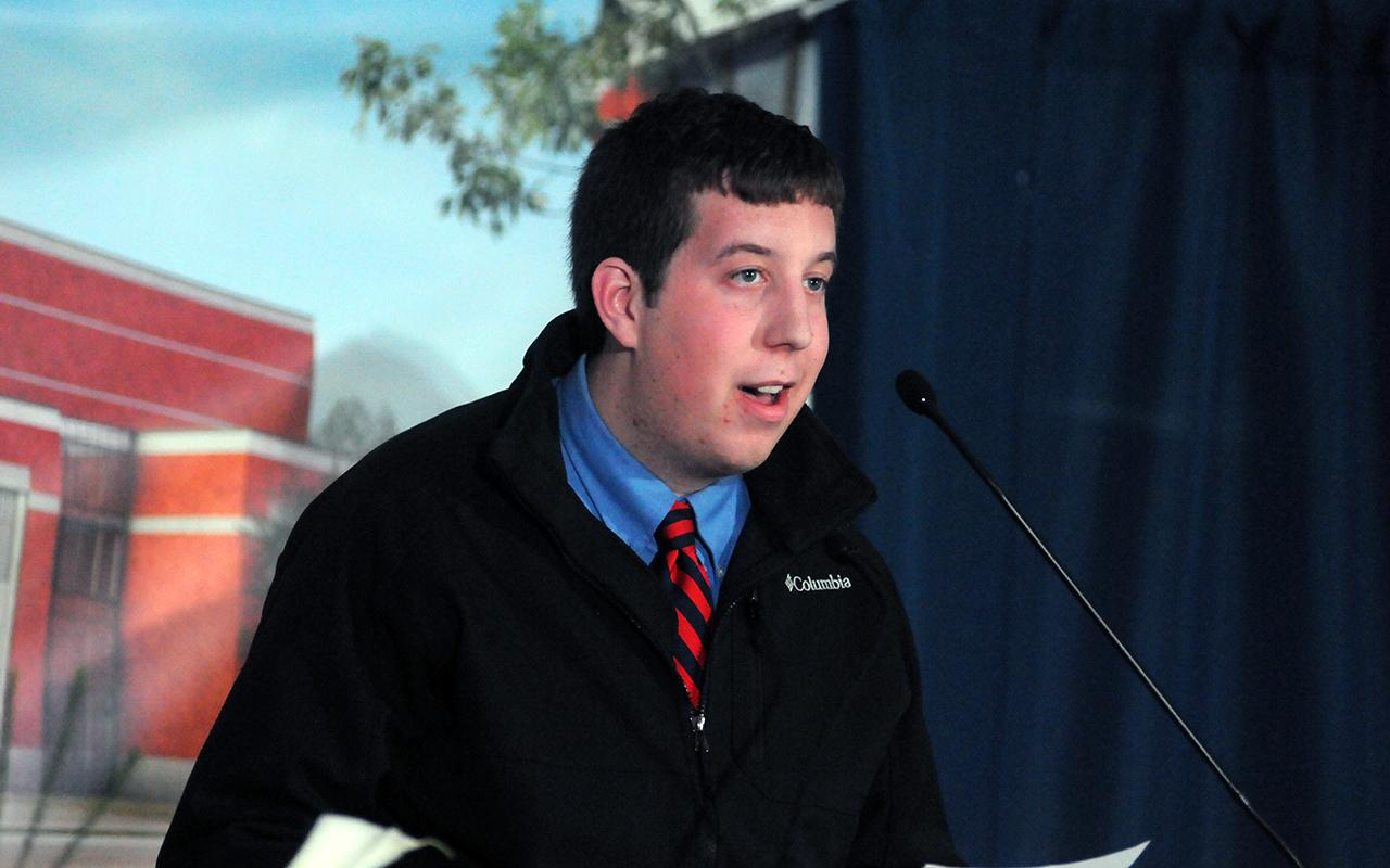 Student Aaron Goodyke '16 speaks from a podium.