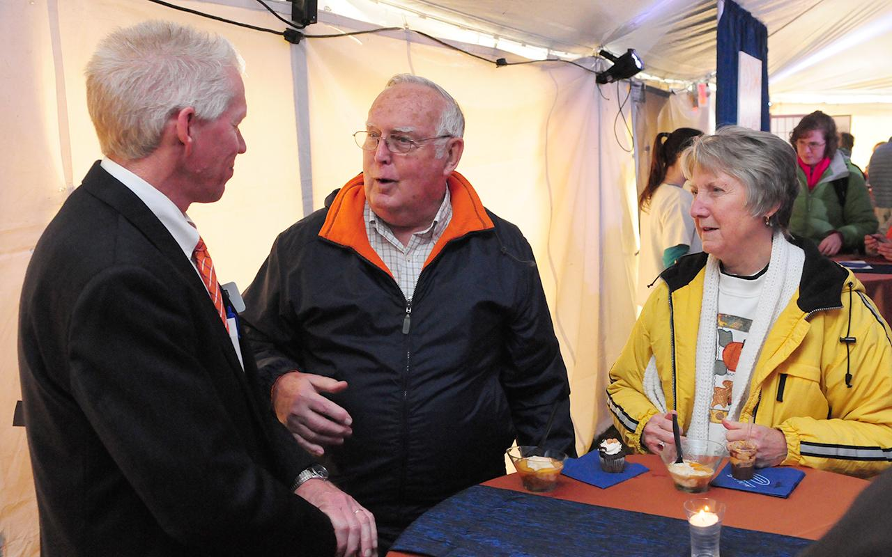 Three adults conversing with each other inside the tent.