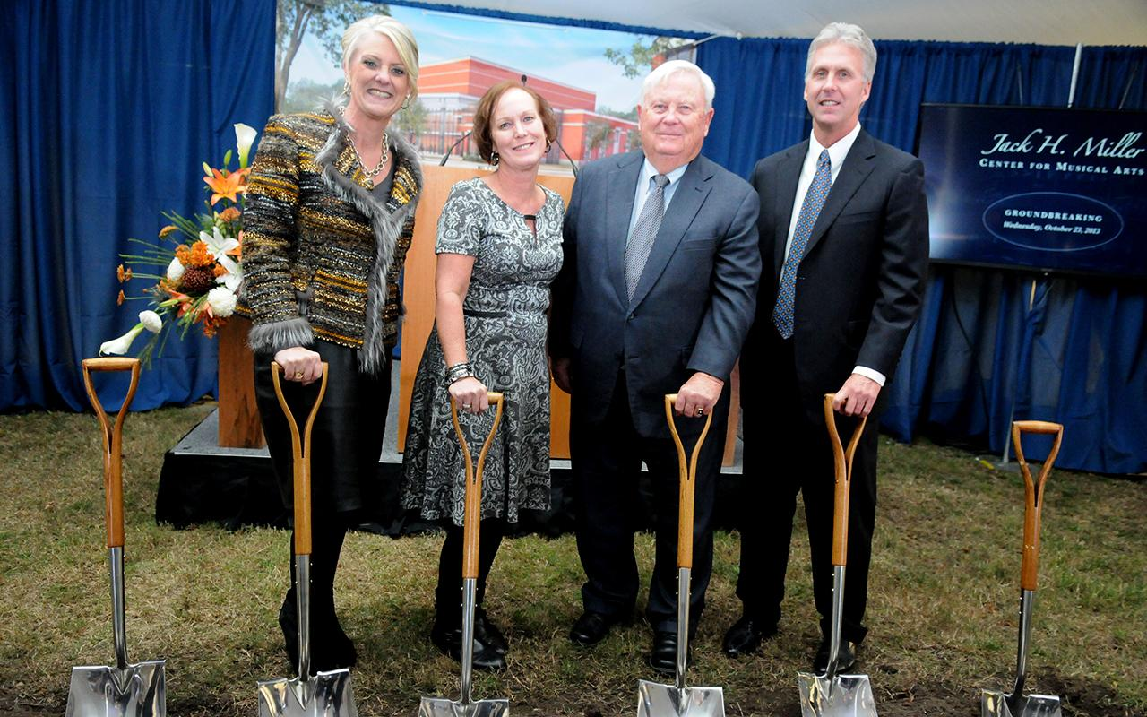 Meg Miller Willit, Sue Miller DenHerder, Jack Miller and Buzz Miller holding shovels.
