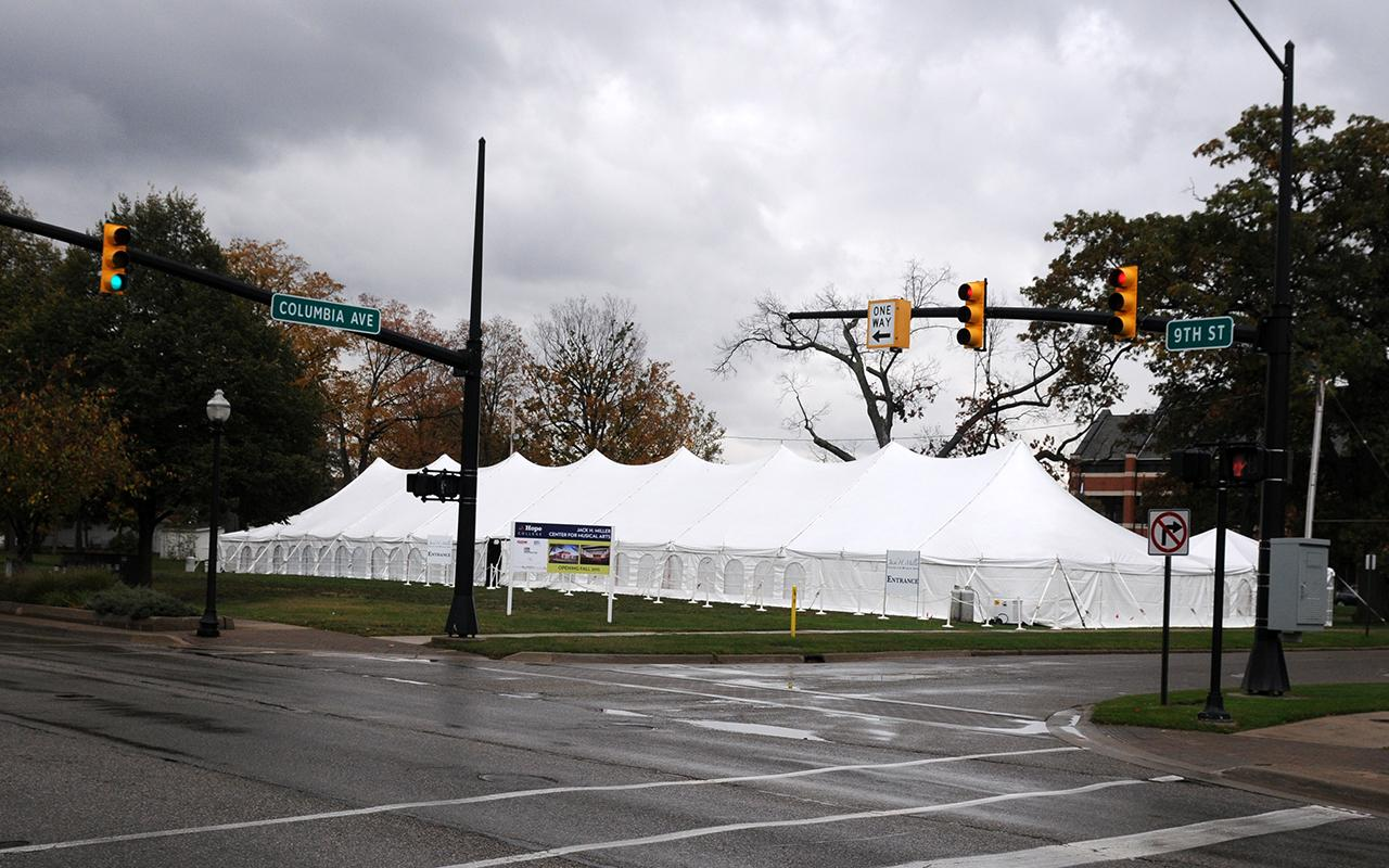 A tent outside for the groundbreaking. Dark clouds are overhead.
