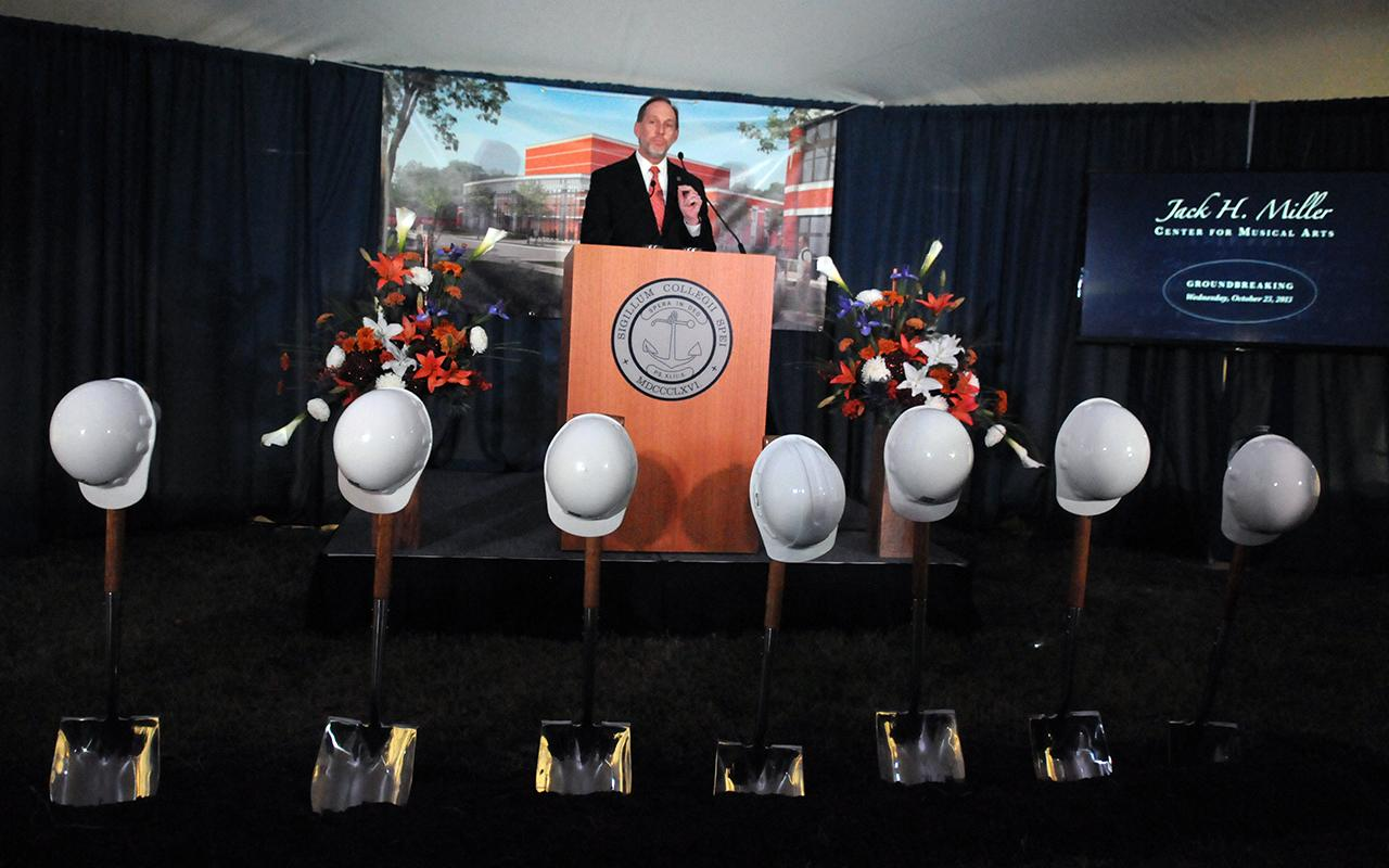 President John Knapp speaking from the podium in front of seven shovels with hardhats on top of each.