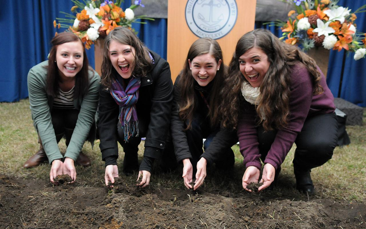 Hope students Kelsey Gustafson, Abigail Johnson, Emily (Young) Suszko and Kristin Baron pick up dirt with their hands.