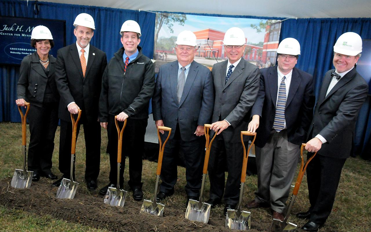 Board of Trustees Chair Mary Bauman, President John Knapp, student Aaron Goodyke, Jack Miller, President Emeritus James Bultman, professor Rob Hodson and HGA Design Architect Bill Blanski hold shovels while wearing hardhats.