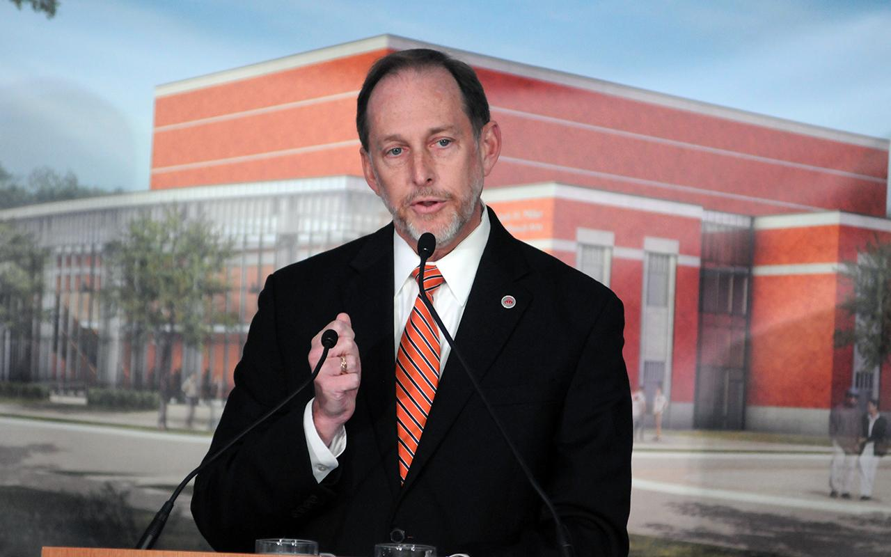 President John Knapp at the podium making a fist while speaking.