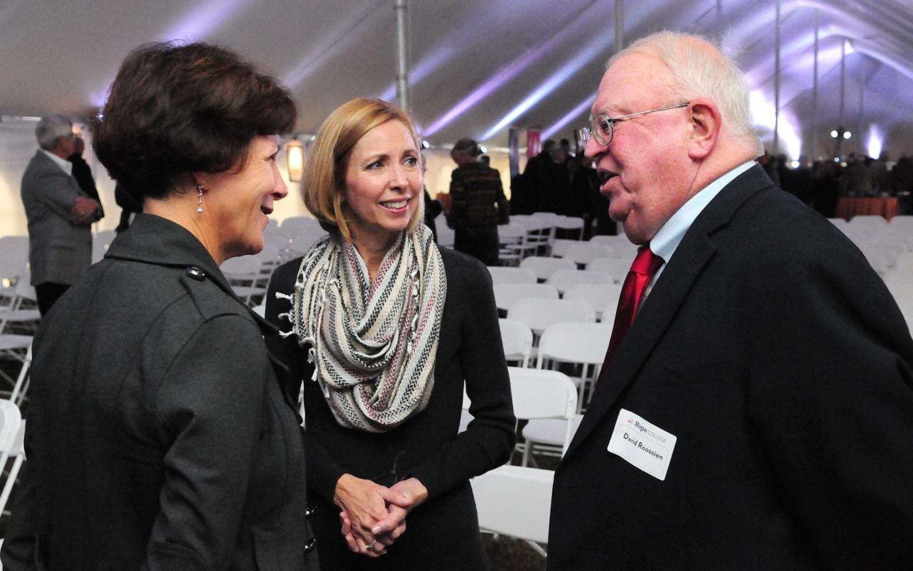 Two adults talk with the president's wife, Kelly Knapp.