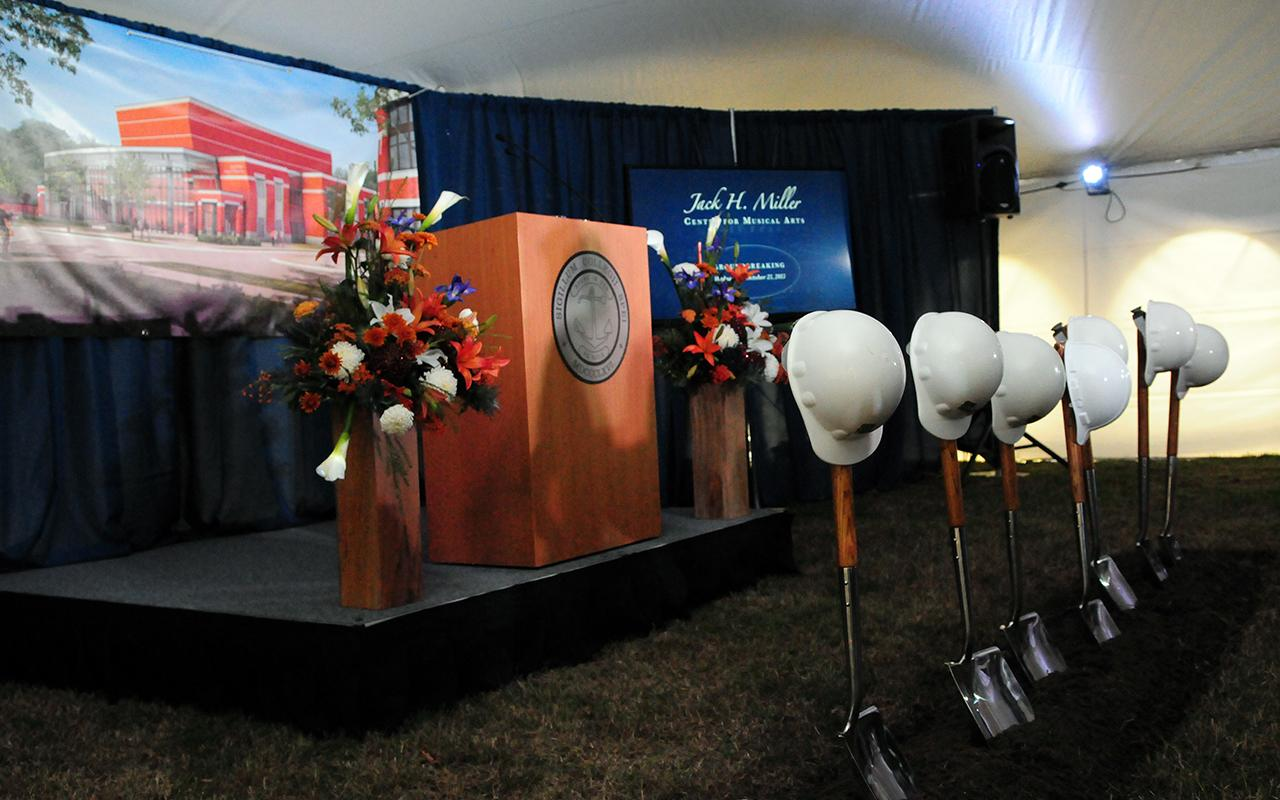 A podium and six shovels with hardhats on the top of each.