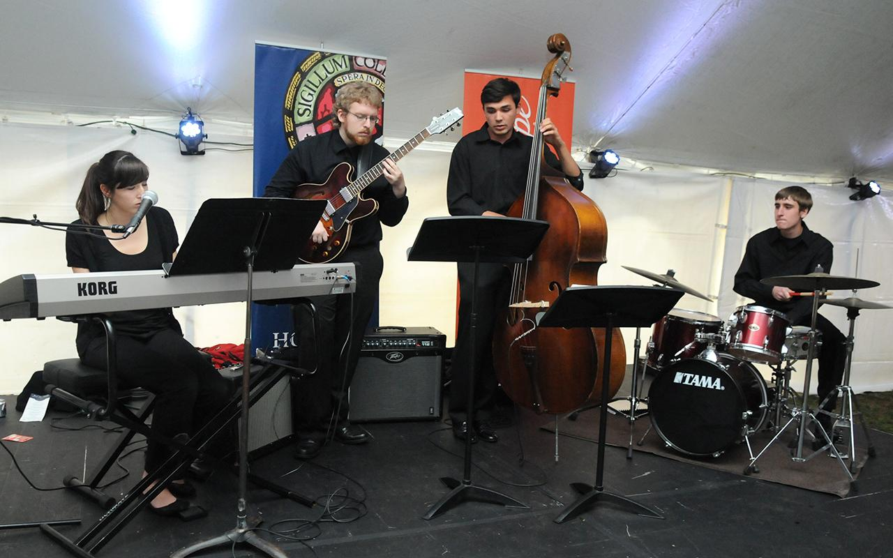 Students Meghan Stagl, Michael Graverson, Jared DeMeester and Andrew Sicard play instruments on a stage in the tent.