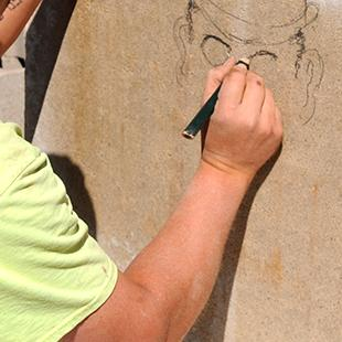 A worker drawing a plan on a smaller concrete slab.