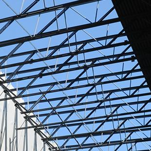 A view from the inside of one of the sections of the building. Poles are securing concrete panels.