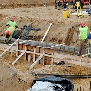Workers laying down the initial foundation pieces.