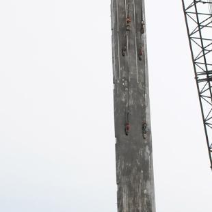 A crane begins to place a concrete panel into place.
