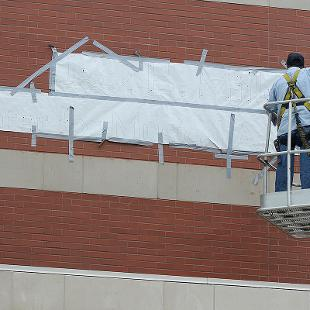 Two workmen on a lift attaching template pattern to place letters on outside of the building spelling out Jack H. Miller Center for Musical Arts