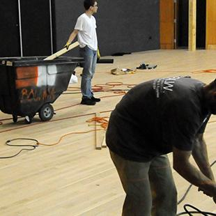 Two men laying new flooring on the main auditorium stage.
