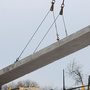 A crane lowering a concrete panel.