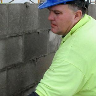 Worker building a brick wall.