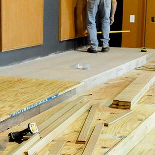 Workers placing the flooring in the auditorium.