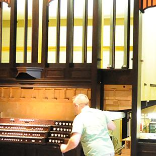 Man works on re-assembling the studio organ from Nykerk Hall of Music.
