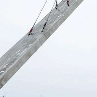 A crane lowering a concrete panel.