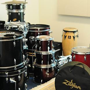 Drums and other musical equipment placed in a room within the building.