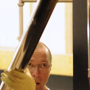 A man placing organ pipes.