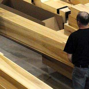 Two people moving organ pipes in the auditorium.