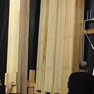 Two men assembling the organ pipes.