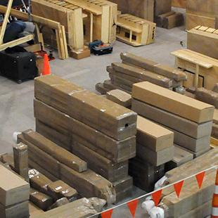 The organ pipes lying on the floor in the auditorium, ready to be assembled.