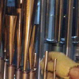 A man securing smaller organ pipes.
