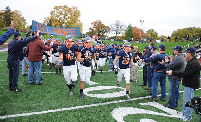 Football players running through a tunnel of people at Ray and Sue Smith Football Stadium.