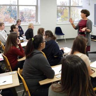 Students engage with a professor in a classroom of Van Zoeren Hall