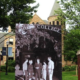 A historic black-and-white photograph held in front of a contemporary shot of the Hope College arch