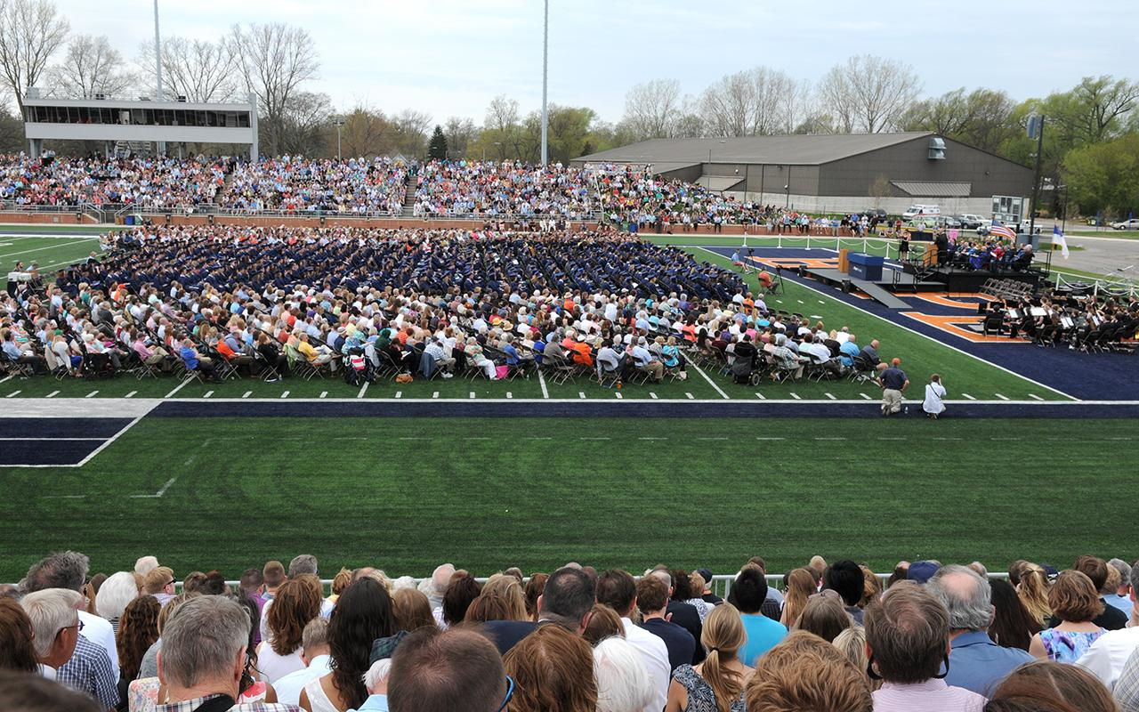 An overview of the Commencement ceremony taken from the stadium stands showing the graduating class and faculty on the field.