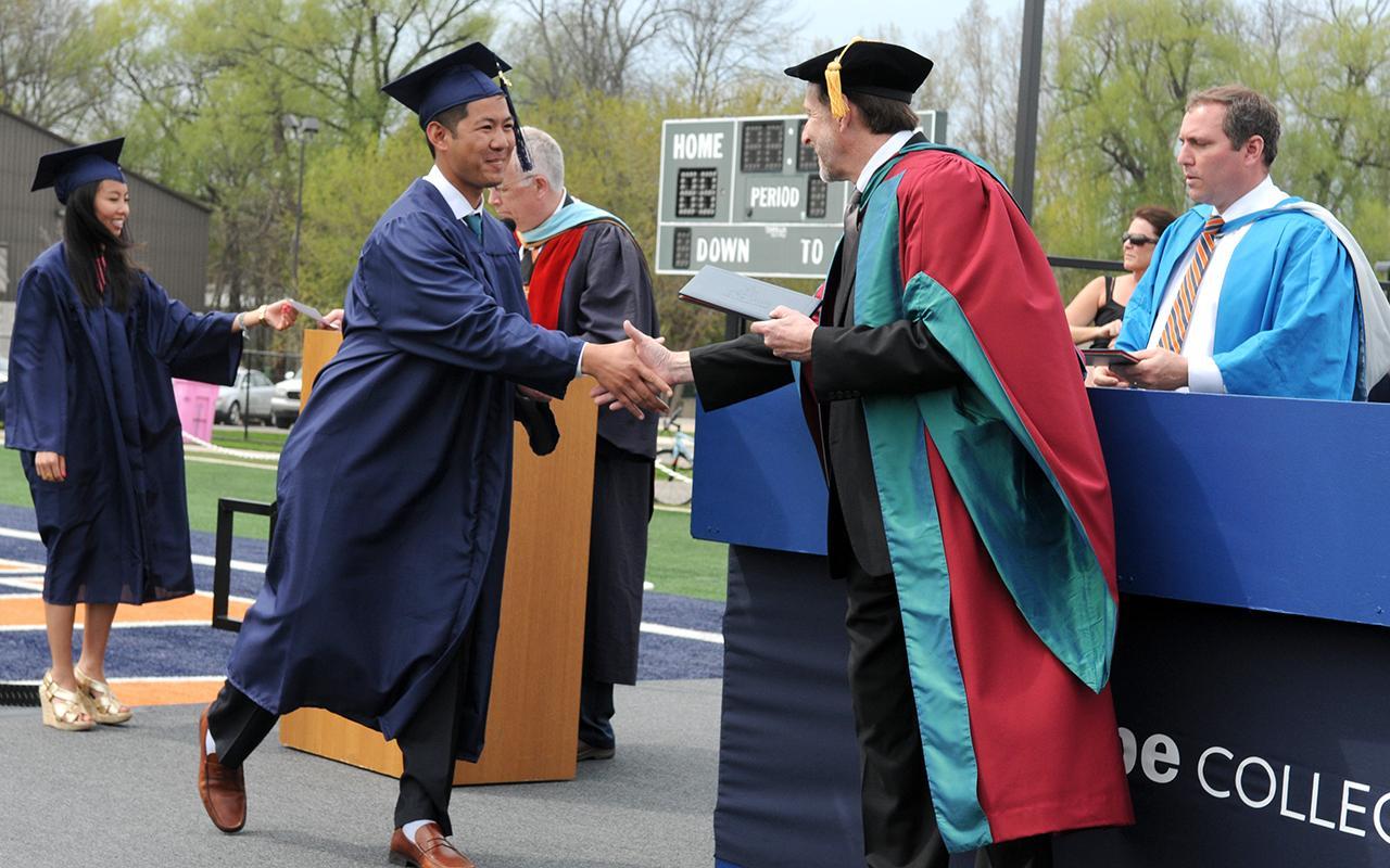 Male student shakes hands with President Knapp on stage as Trygve Johnson watches.