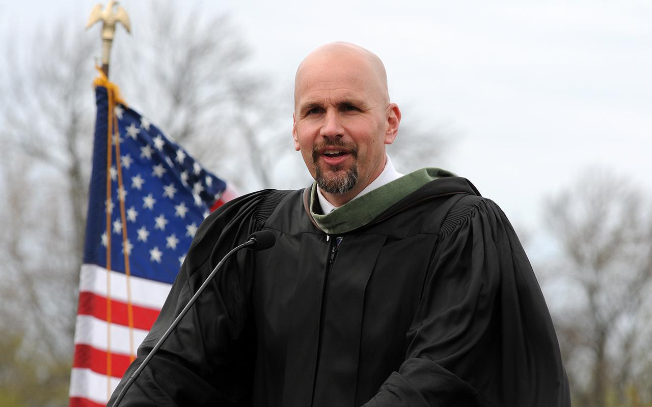 Professor and Co-Athletic Director Tim Schoonveld gives the Commencement address with American flag in the background.