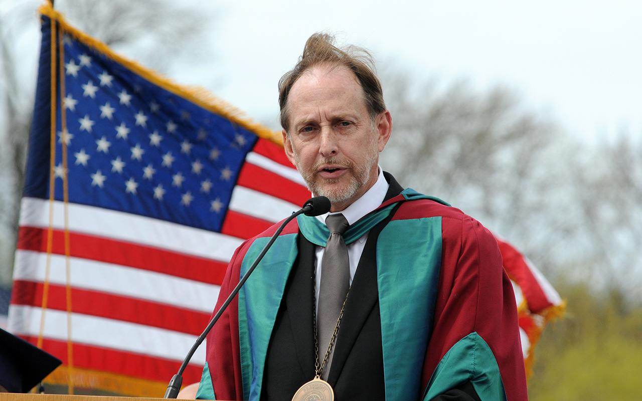 President Knapp speaks during Commencement with the American flag behind him on the stage.