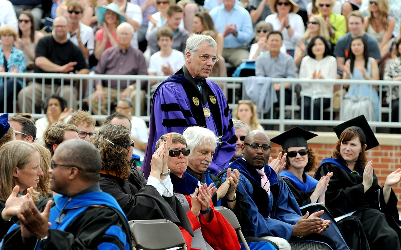 Retiring Professor John Shaughnessy standing in the faculty section with families applauding in the stadium.