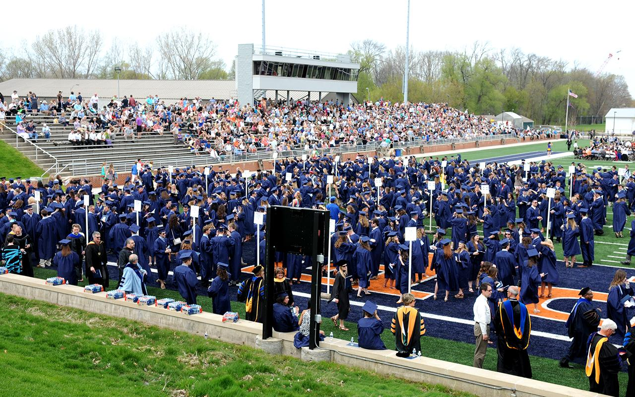 Students gather on the end zone of the football field waiting for the Commencement procession.