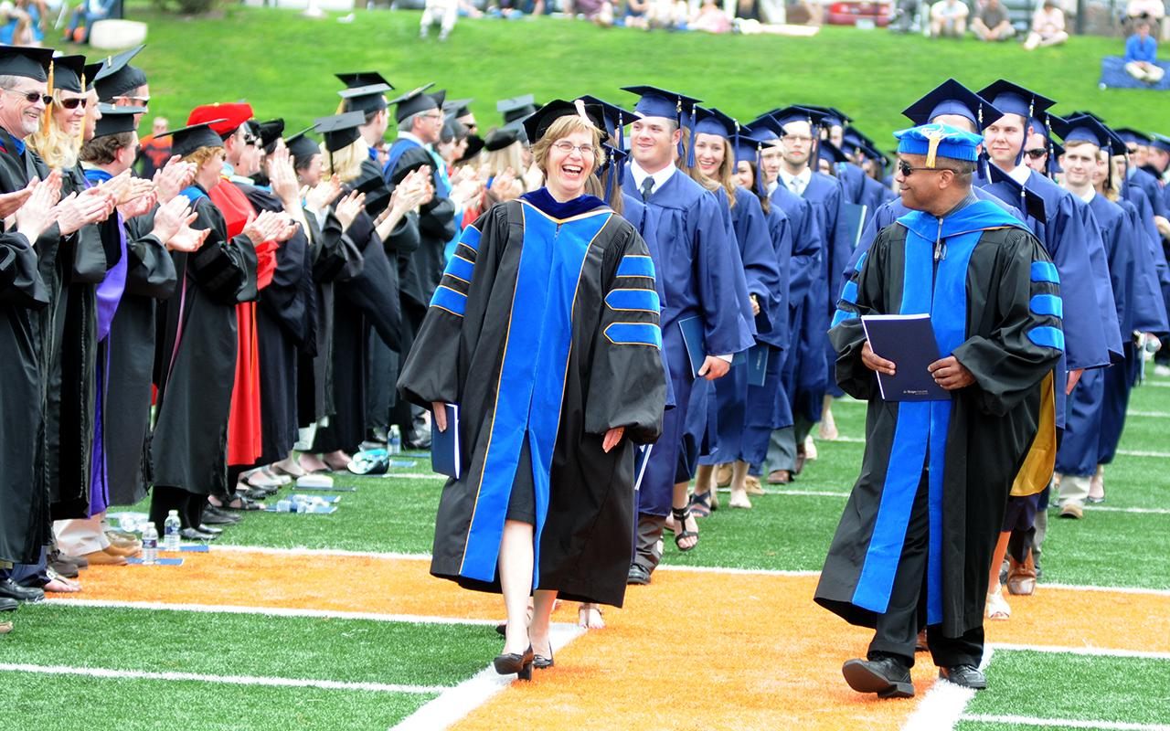 Marshals Joanne Stuart and Fred Johnson lead the graduates on the football field past the applauding faculty.