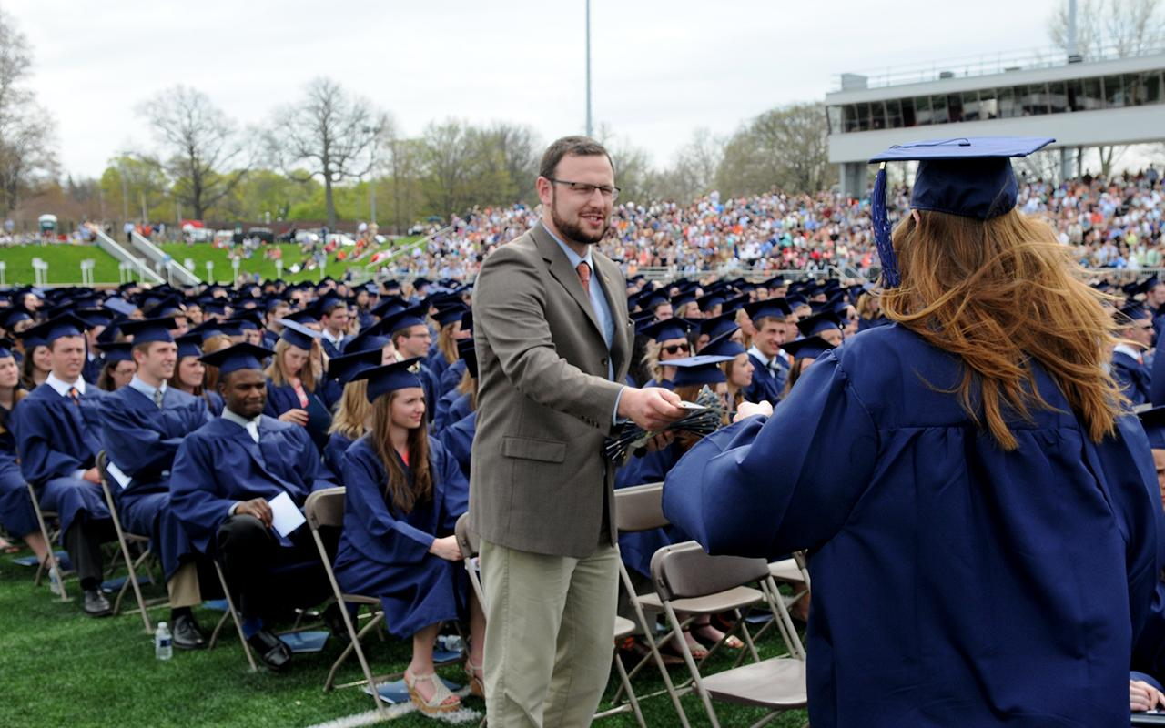 Alumni Director Scott Travis presents Alumni Association pins to new graduates as they come off the stage after receiving their diploma.