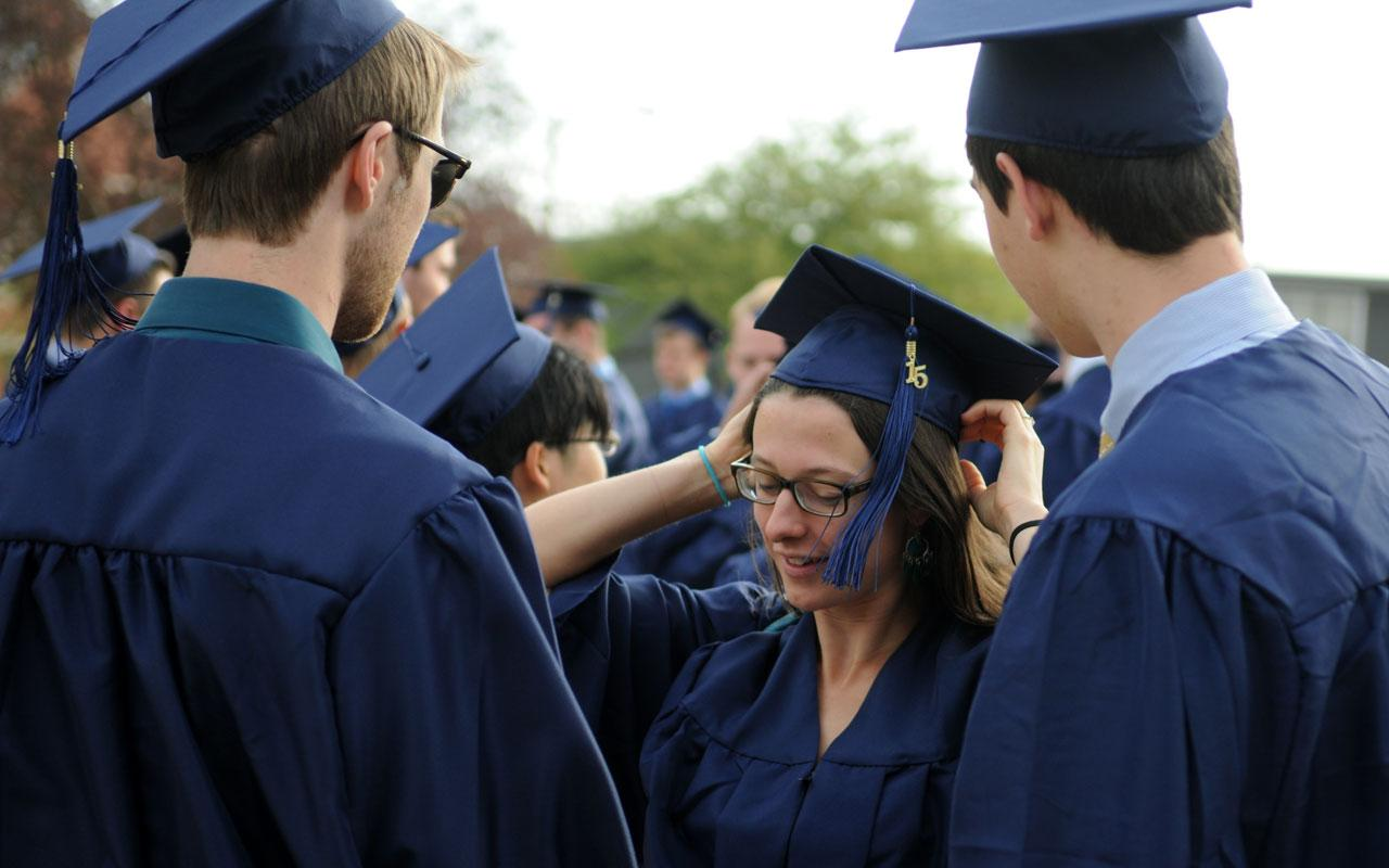 Female student adjusts graduation cap in group of seniors outside the DeWitt Center