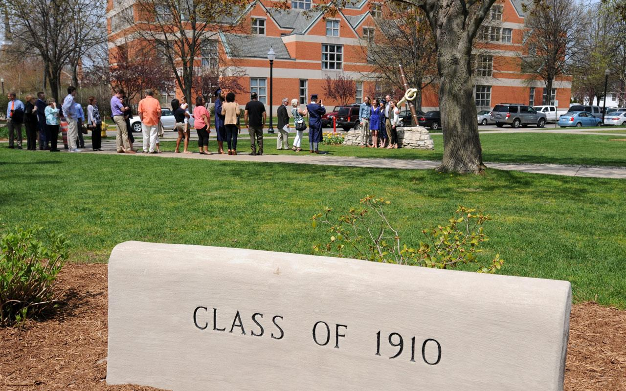 Class of 1910 marker in foreground with people milling around outside following the Baccalaureate Service.
