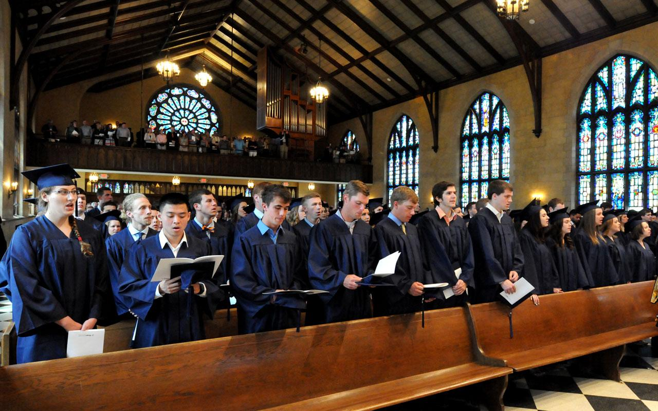 Graduating Seniors attending Baccalaureate Service stand in pews, taken from the front of Dimnent Memorial Chapel.