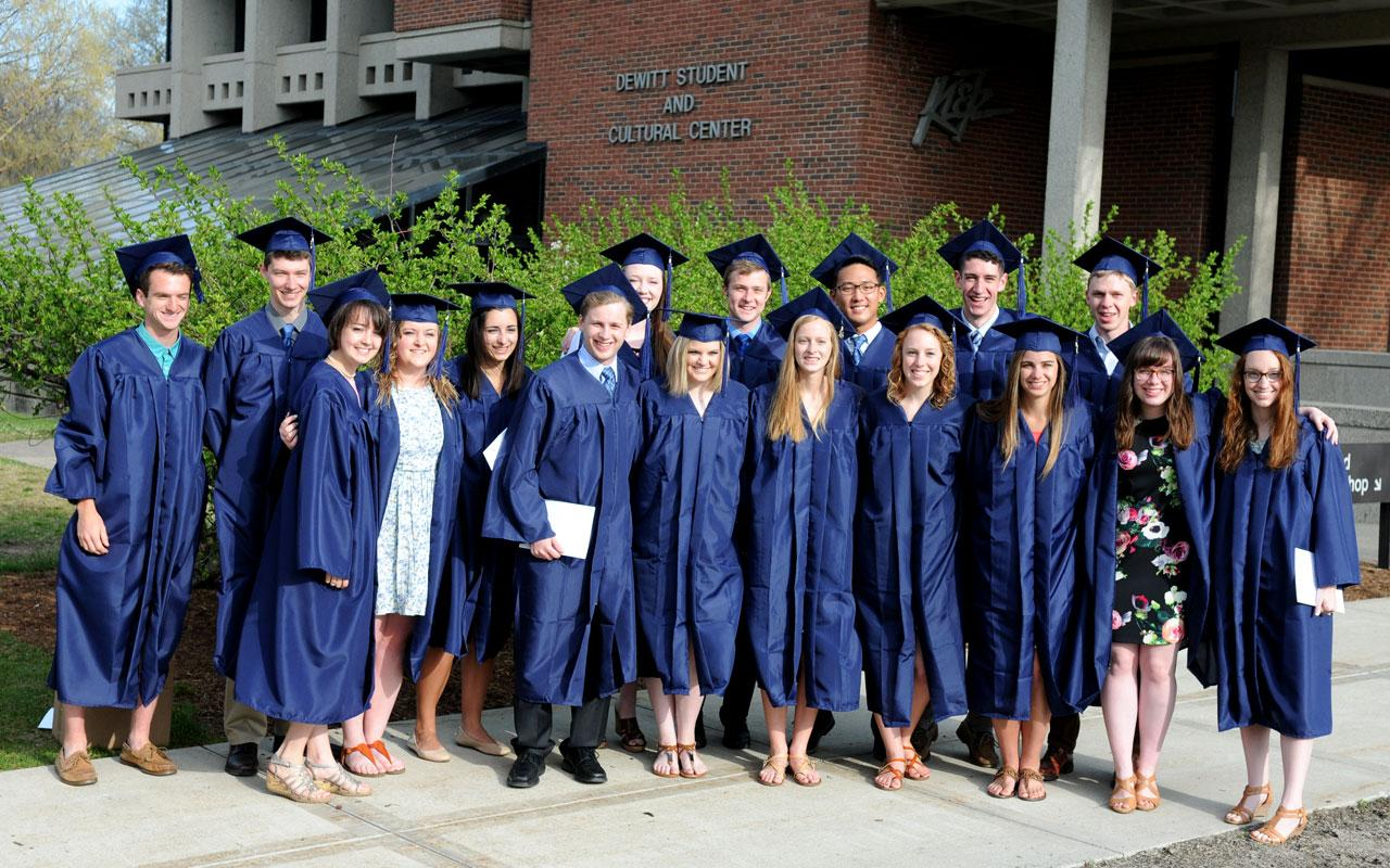 Groups of students in caps and gowns pose for a photo outside of the DeWitt Center.