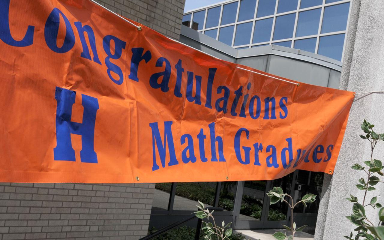 "Sign proclaiming ""Congratulations Math Graduates"" hung outside Van Zoeren Hall."