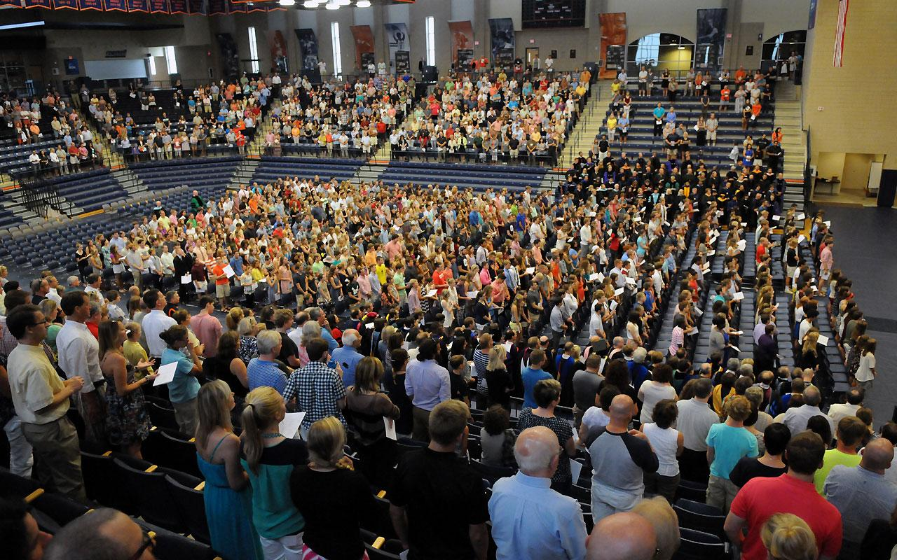 An overview photo of the Richard and Helen DeVos Fieldhouse filled with new students, family members and faculty participating in the  Opening Convocation.