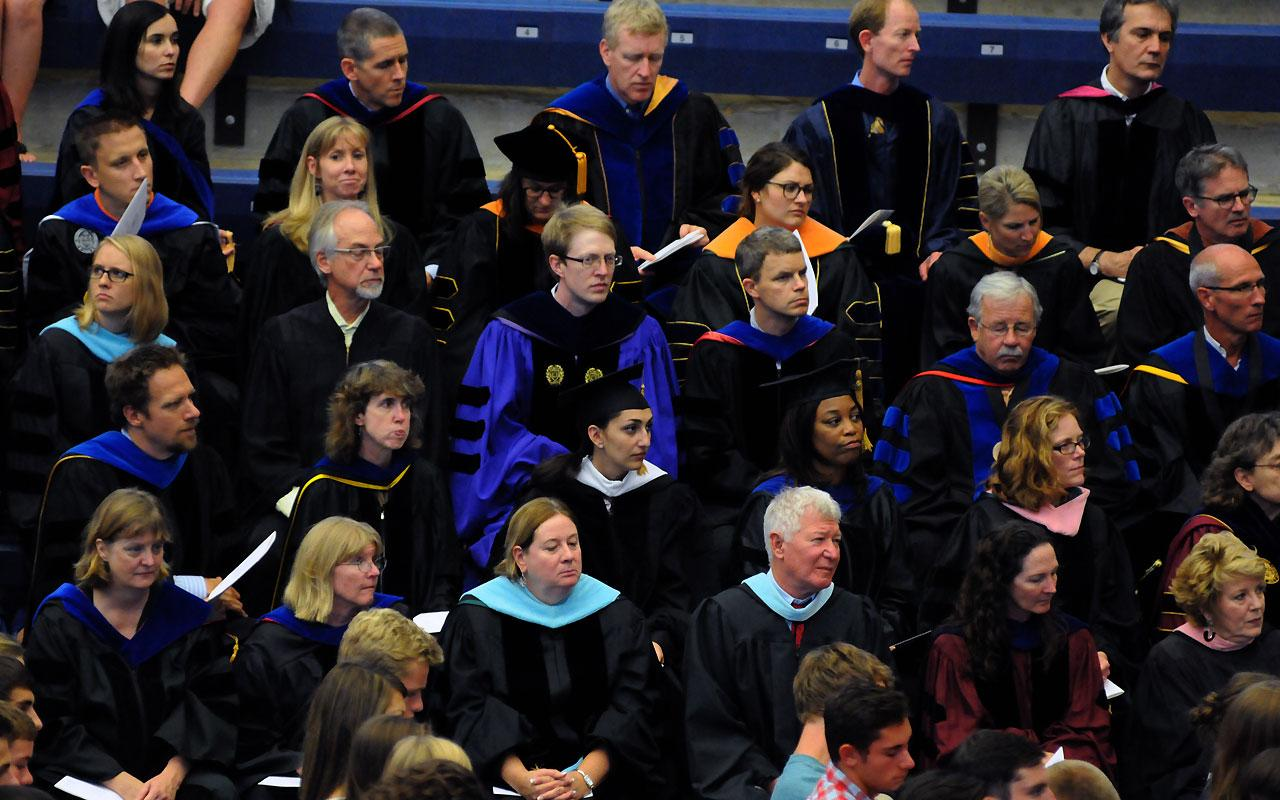 The faculty are seated in the stands of the Richard and Helen DeVos Fieldhouse in their academic robes.