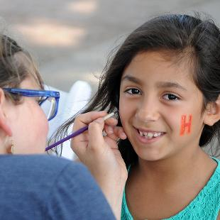 A female college student painting a design on the face of a young girl.