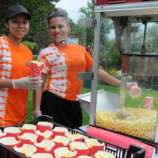 Two ladies making popcorn to give away during the picnic.